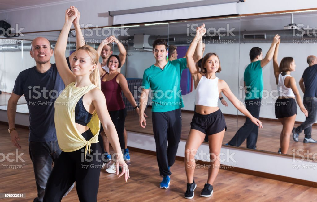Group of positive people dancing bachata together stock photo