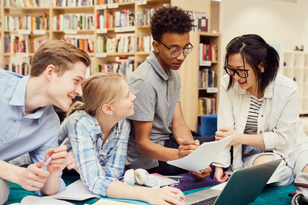 Group of positive young multi-ethnic students sitting in modern library and viewing curriculum while preparing for classes stock photo