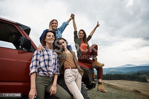 1131372580 istock photo Group of positive young women standing near their car 1131372565