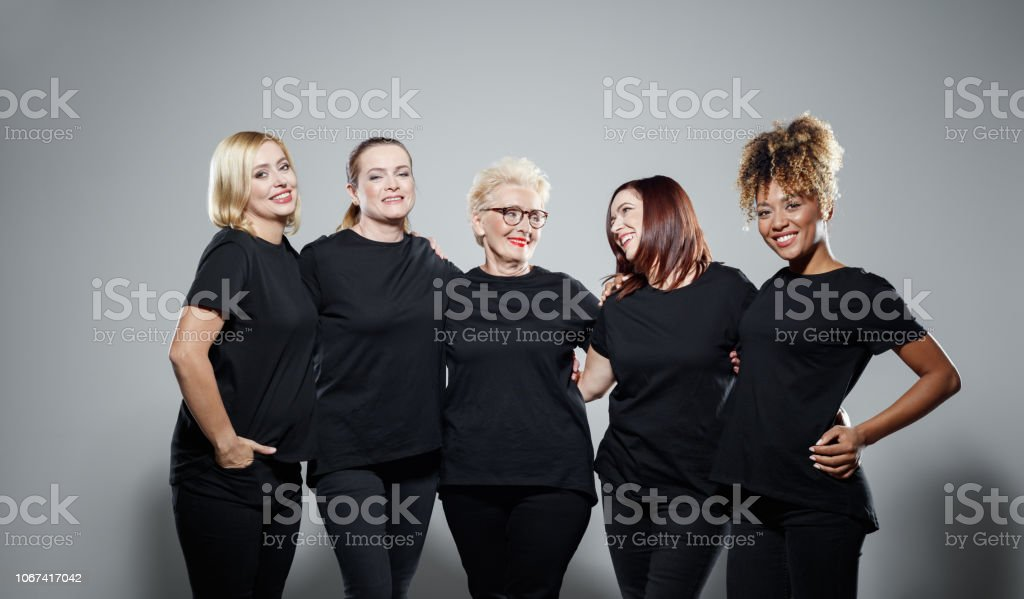 Group of powerful women Portrait of pleased women wearing black clothes, embracing against grey background and smiling at camera. Studio shot. Activist Stock Photo
