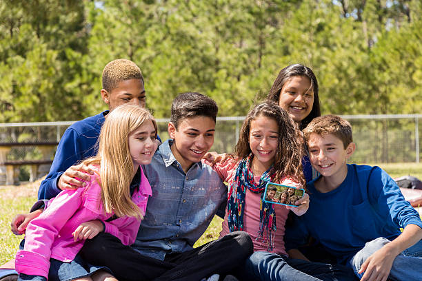 Group of pre-teenage friends take 'selfie' with smart phone. stock photo