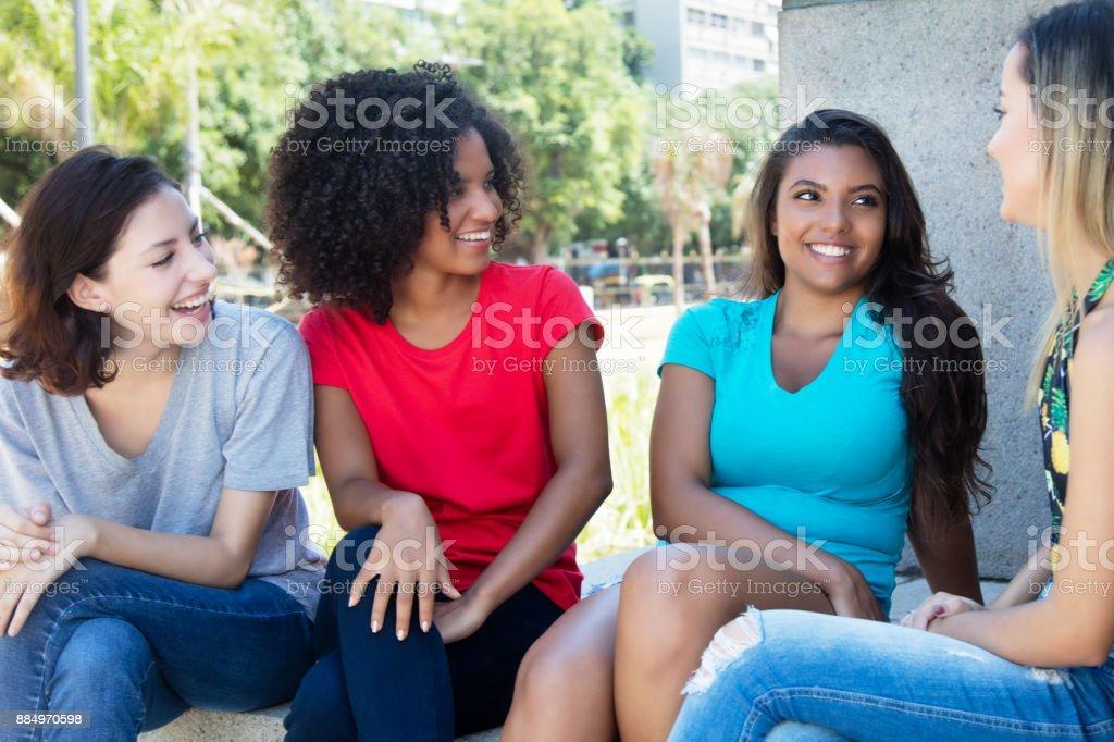 Grupo de bem femininos jovens adultos falando ao ar livre - foto de acervo
