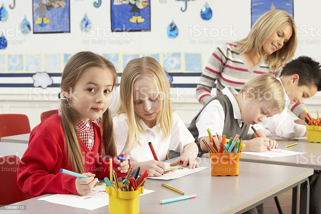 Group Of Primary Schoolchildren And Teacher Having lesson royalty-free stock photo