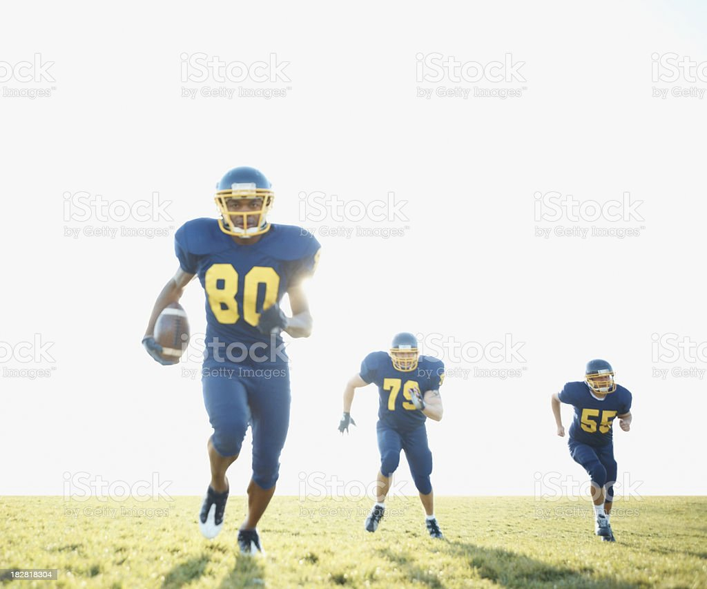 Group of Pro American Footballers running with football royalty-free stock photo