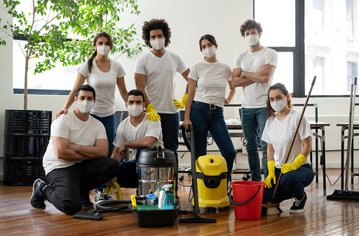 Latin American group of professional cleaners working at an office wearing facemasks during the COVID-19 pandemic
