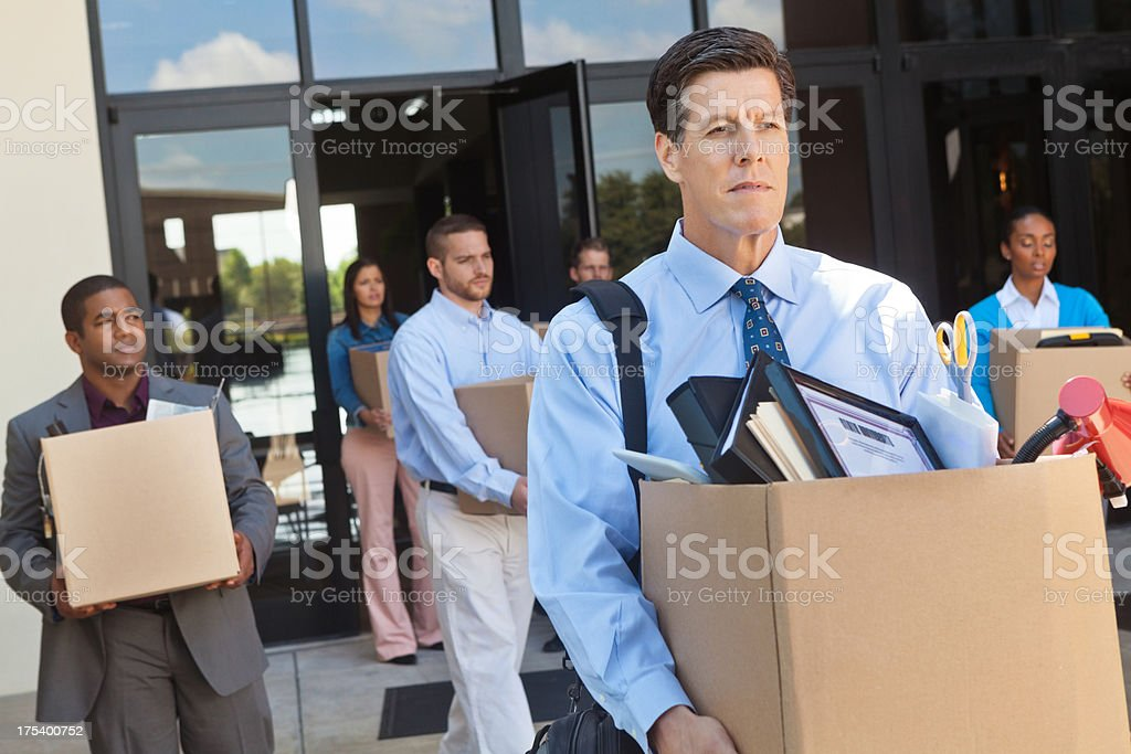 Group of professionals leaving office after layoff or being fired stock photo