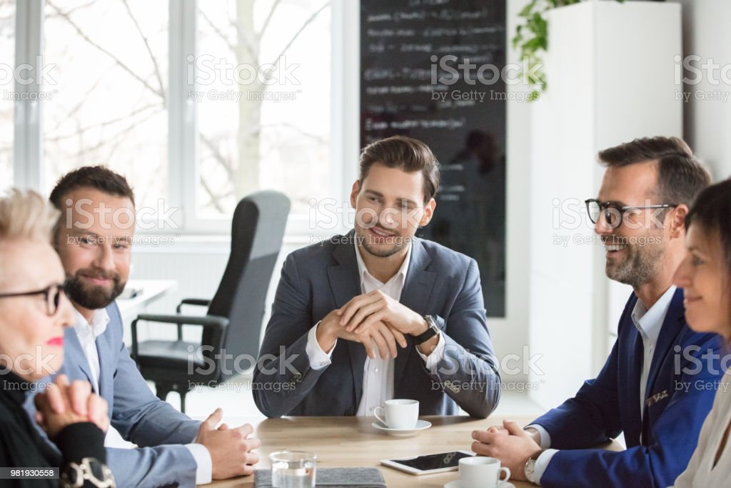 Group of professionals meeting in office Group of professionals discussing during a meeting in office. Businessman and businesswoman sitting at conference table and discussing over new project. Active Seniors Stock Photo