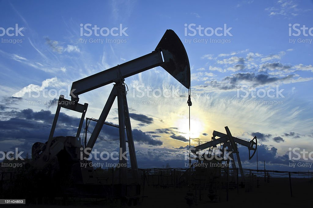Group of pump-jacks drilling in silhouette stock photo