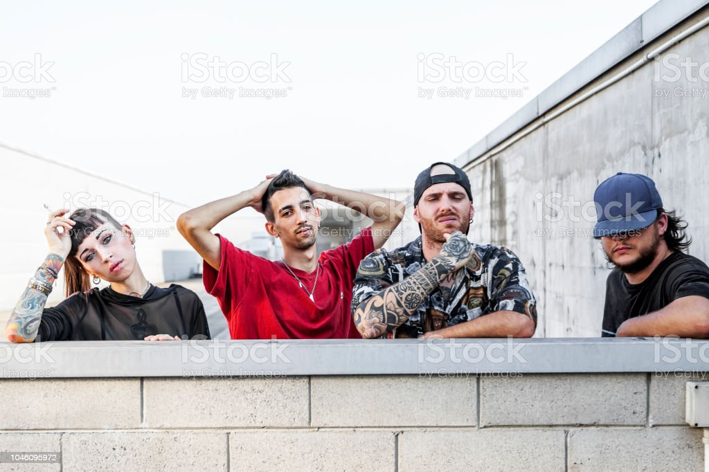 group of rappers posing leaning against the wall stock photo