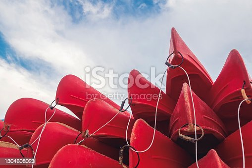 group of red kayaks piled up against each other on the shore seen from below with a blue sky in the background