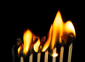 istock Group of red match burning isolated on black background. 1279186031