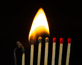 istock Group of red match burning isolated on black background. 1279186408