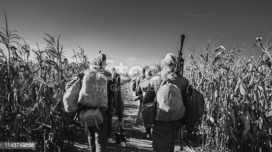 1143756392 istock photo Group Of Re-enactors Dressed As World War II Russian Soviet Red Army Soldiers Marching Through Autumn Cornfield. Photo In Black And White Colors. Soldier Of WWII WW2 Times 1143749598