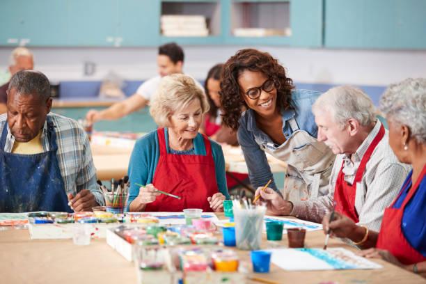 grupo de ancianos jubilados asistiendo a clase de arte en el centro comunitario con el profesor - clase de arte fotografías e imágenes de stock