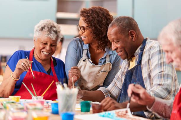 grupa emerytowanych seniorów uczęszczających na zajęcia artystyczne w centrum społeczności z nauczycielem - dojrzały zdjęcia i obrazy z banku zdjęć