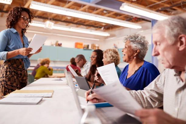 group of retired seniors attending it class in community centre with teacher - pensionati lavoratori foto e immagini stock