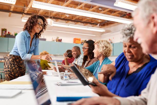 與教師一起參加社區中心 it 班的退休老人群體 - 成年人 個照片及圖片檔