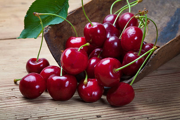 A group of ripe cherries on a wooden table stock photo