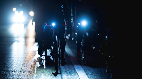 group of road bike riders at night, they turn on the headlights.noise in image.