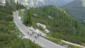 Group of male and female road bikers riding on mountain road surrounded by trees and mountains.