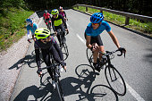 Group of male and female cyclists riding road bikes on mountain road.