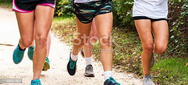 976685710 istock photo Group of runners legs running on a path in a park 1199531507