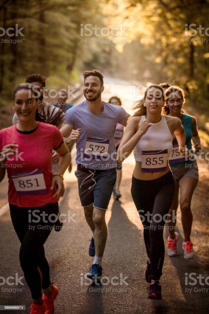 Grupo de corredores que participam em uma corrida de maratona pela floresta. - foto de acervo