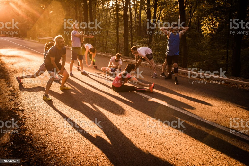 Group of runners warming up before the marathon on a road at sunset. stock photo