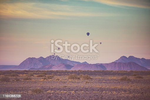 Tourist Hot Air Balloons over the Namib-Naukluft Nature Reserve Namibian Desert with sand dunes and pink coloured mountains and a dramatic early morning vibrant coloured sky in Namibia Africa