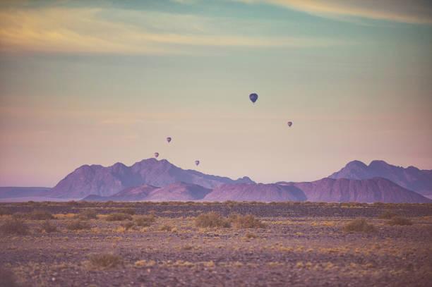 eine gruppe von safari heißluftballons über rosa wüste landschaft am frühen morgen - namib wüste stock-fotos und bilder