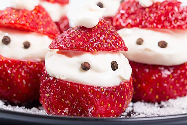 group of santa-klaus from berries of strawberry and cream - weihnachtsmannhüte aus erdbeeren stock-fotos und bilder