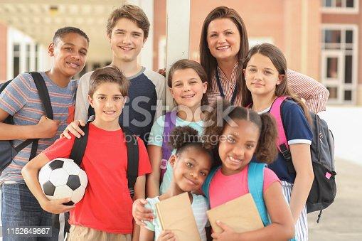 istock Group of school children, friends and teacher on campus. 1152649867