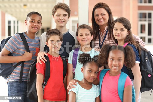 istock Group of school children, friends and teacher on campus. 1165536359