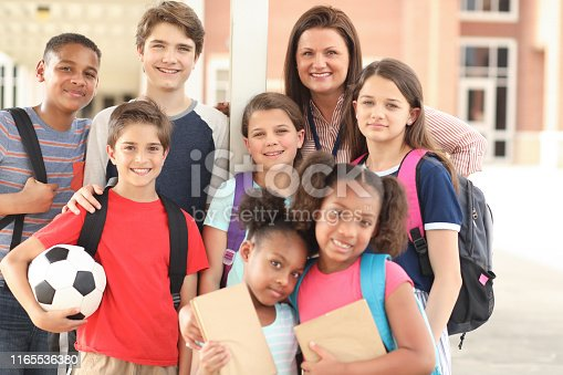 istock Group of school children, friends and teacher on campus. 1165536380