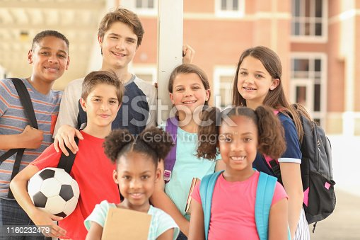 476098743 istock photo Group of school children, friends together on campus. 1160232479