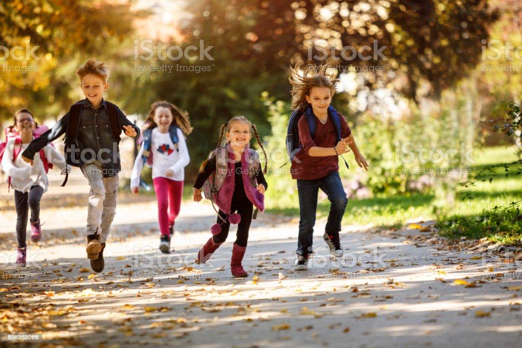 Group of school children running outside stock photo