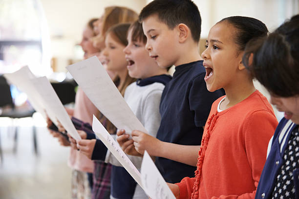 group of school children singing in choir together - performing arts event stock pictures, royalty-free photos & images