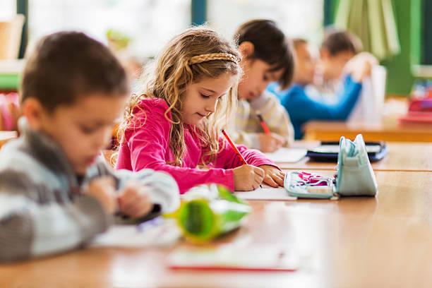 gruppe der schüler sitzen im klassenzimmer und schreibtisch. - grundschule stock-fotos und bilder