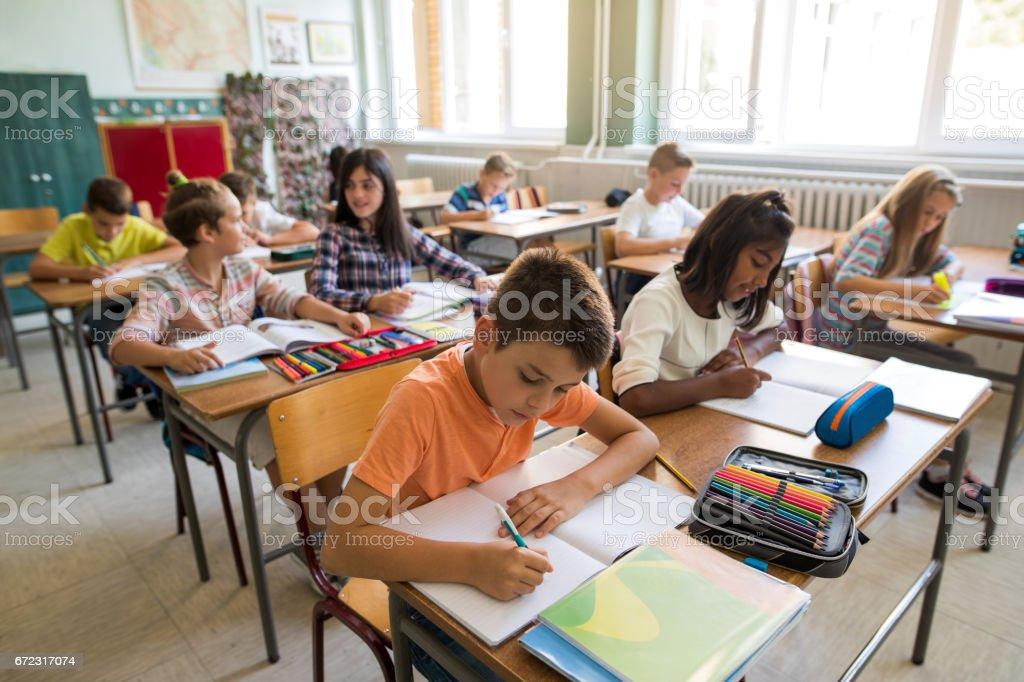 Grupo de crianças da escola estudando em sala de aula. - foto de acervo