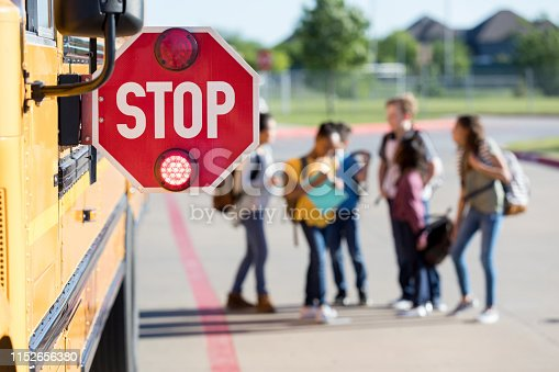 Before getting inside the school bus, a group of junior high school students stand near the bus and talk together.