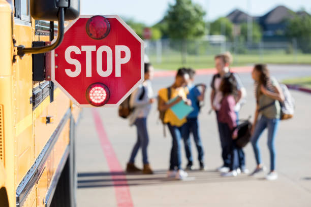 group of school children talk outside bus - school buses stock pictures, royalty-free photos & images