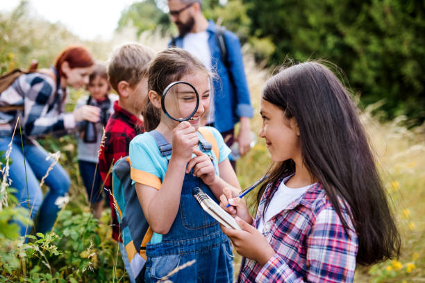 Group of school children with teacher on field trip in nature, learning science. stock photo
