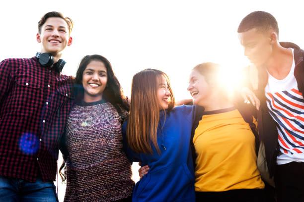 groep schoolvrienden buitenshuis armen rond elkaar, saamhorigheid en communautair concept - tiener stockfoto's en -beelden