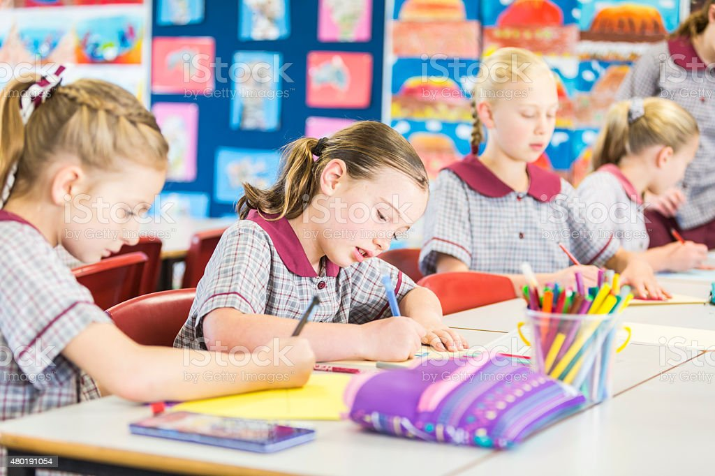 Group of School Girls Doing Work in the Classroom stock photo