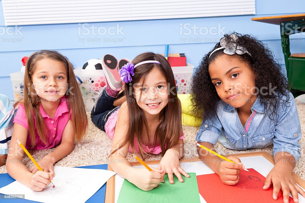 Group of school girls enjoy working on project in classroom. stock photo