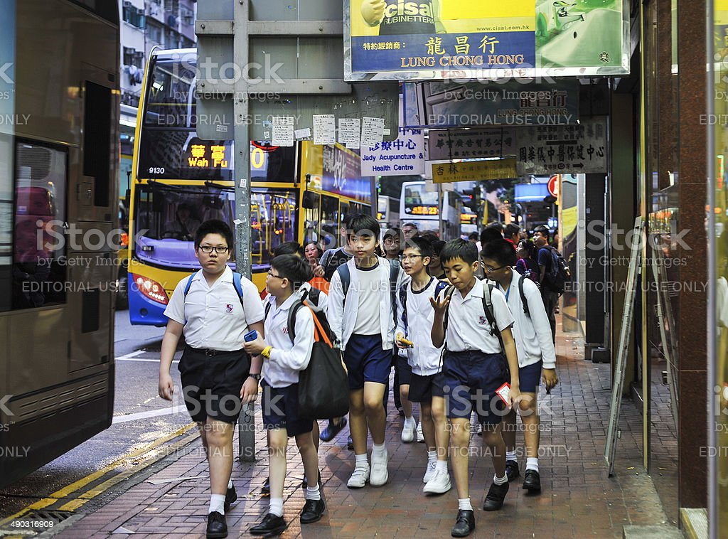 Group of school kids in uniforms walking on the street stock photo