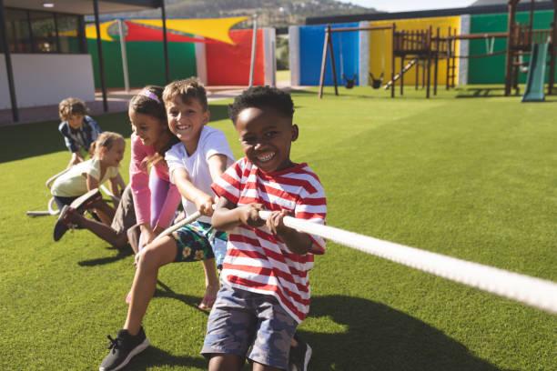 group of school kids playing tug of war - дети стоковые фото и изображения