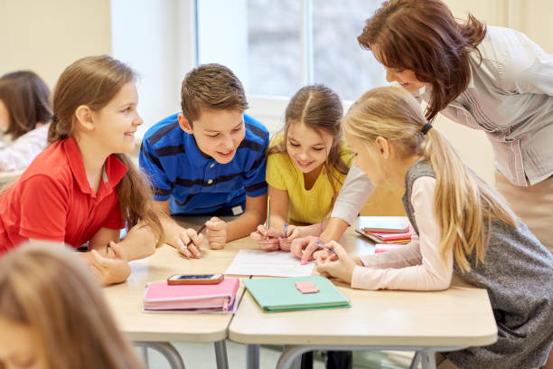 group of school kids writing test in classroom education, elementary school, learning and people concept - teacher helping school kids writing test in classroom schoolboy stock pictures, royalty-free photos & images