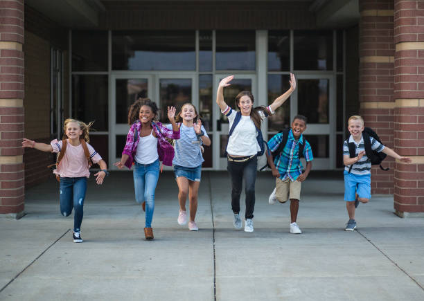 Group of school school kids running as they leave the school building stock photo