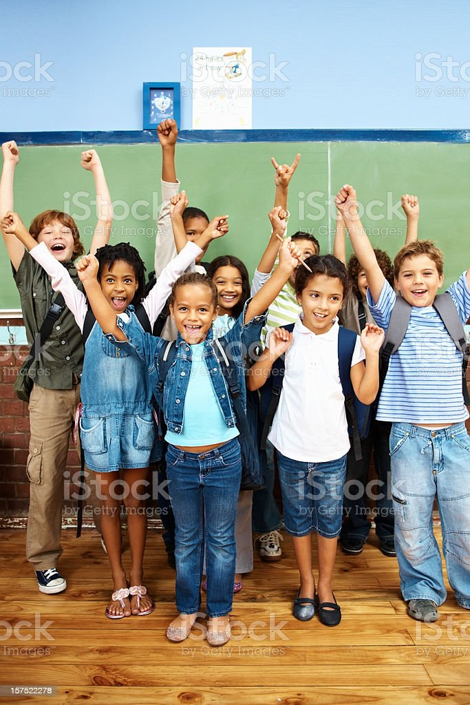 Group of school students with their hands raised royalty-free stock photo